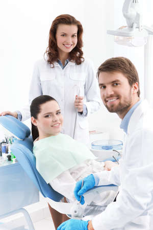 customer assistant: Dentist, assistant and the patient are ready for treating carious teeth
