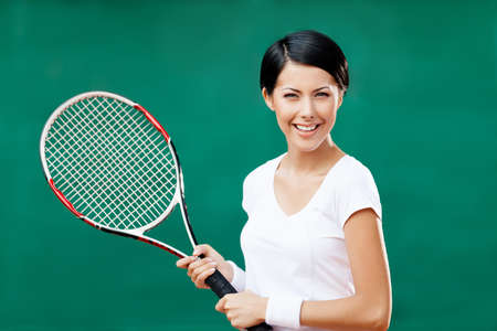 Portrait of successful female tennis player with racquet at the tennis court Stock Photo - 16040685