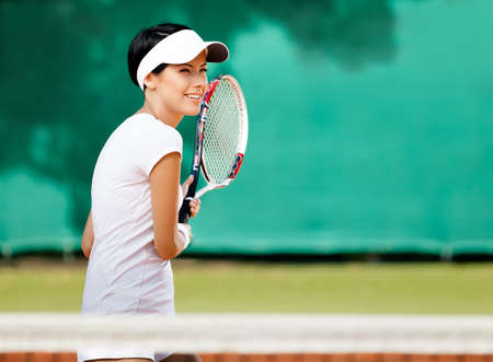 Sportswoman at the tennis court with racquet. Leisure photo