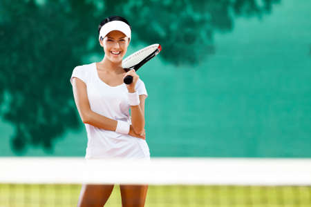 Young sportswoman with racquet at the tennis court. Healthy lifestyle photo