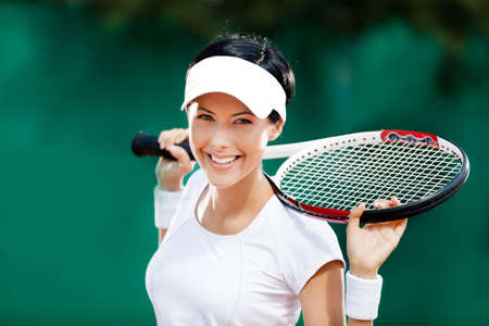 Pretty sportswoman with racket at the tennis court. Healthy lifestyle photo