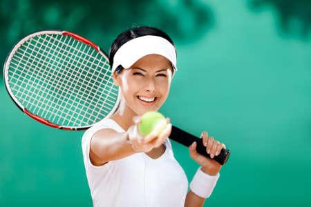 raqueta de tenis: Mujer en ropa deportiva sirve pelota de tenis. Competencia