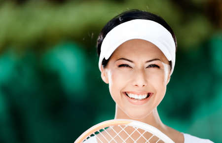 Close up of happy woman with tennis racket at the tennis court. Victory photo