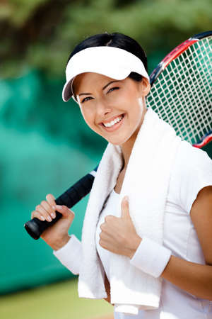 Young female tennis player with towel on her shoulders. Active pastime photo