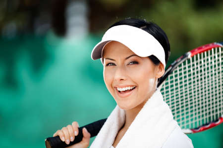 Tennis player with towel on her shoulders. Active pastime photo