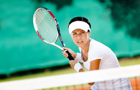 Woman in sportswear playing tennis. Training photo