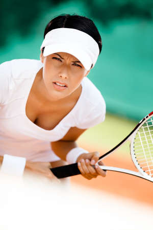 Woman in sportswear playing tennis. Match photo