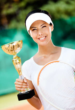 Tennis player won the cup at the sport competition. Victory photo