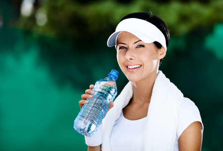 Sporty woman with bottle of water after tennis contest Stock Photo - 16041298