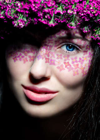Close-up portrait of young beautiful blue-eyed woman with flowered wreath and creative make up photo