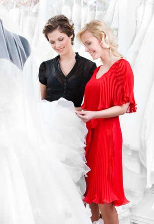 bridal salon: Girl hesitates about wedding gown. Shop assistant advises the client to select a proper dress