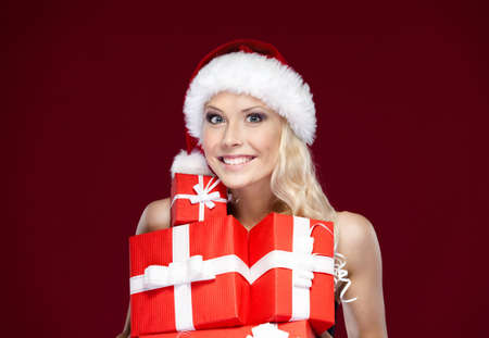 Pretty lady in Christmas cap hands a set of gifts wrapped with red paper, isolated on purple photo