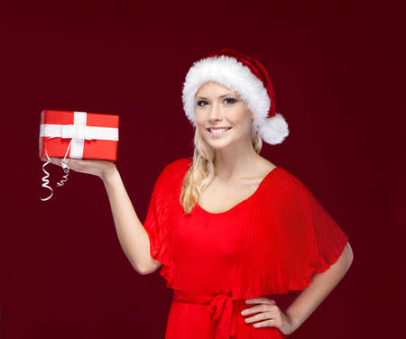 Pretty girl in Christmas cap hands a present with white bow, isolated on purple Stock Photo - 16240909