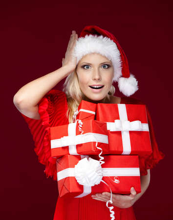 Pretty girl in Christmas cap holds a set of presents, isolated on purple Stock Photo - 16244289