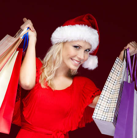 Young woman in Christmas cap hands paper packets, isolated on purple Stock Photo - 16243847