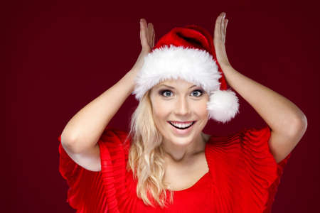Pretty woman in Christmas cap puts her hands on the head, isolated on purple Stock Photo - 16244563