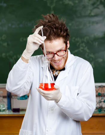 Mad professor adds something to the flask with red liquid in his laboratory photo