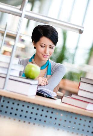Estudiante femenino con manzana verde estudios en la sala de lectura de la biblioteca. Proceso de la educación Foto de archivo - 16244281