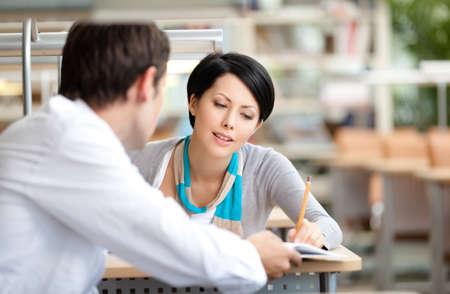 guardar silencio: La mujer se comunica con el hombre joven que muestra su algo en el libro que se sienta en el escritorio en la biblioteca