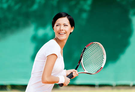 Portrait of successful tennis player with racket at the tennis court photo