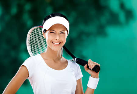 Successful sportswoman with racquet at the tennis court. Healthy lifestyle photo