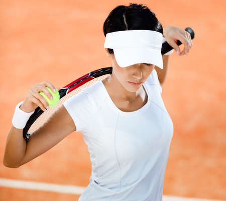 Woman in sports wear keeps tennis racket and ball on her shoulders at the clay tennis court. Leisure photo