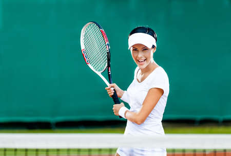 Woman in sportswear plays tennis at competition photo