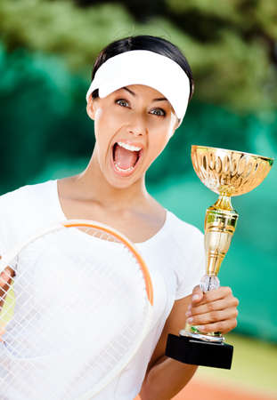 Young female tennis player won the cup at the sport competition. Victory photo