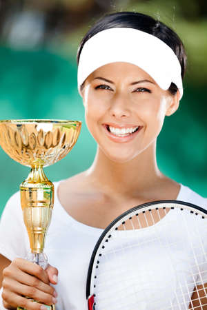 Tennis player won the cup at the sport match. Trophy photo
