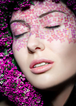 Close up portrait of model with flowered wreath and fashion makeup with eyes shut photo