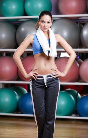 Loosing weight woman in fitness gym with shelves of gym balls photo