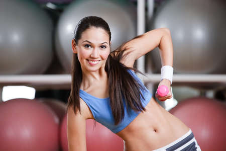 Young woman training with dumbbells in gym to have strong muscles photo