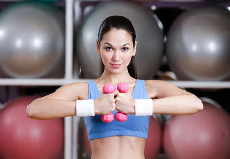 muscular system: Young woman training her muscular system with dumbbells in gym