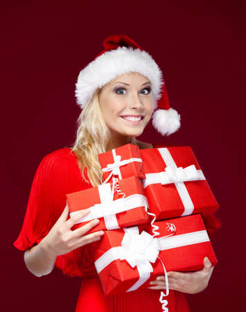 Pretty woman in Christmas cap hands a set of presents, isolated on purple photo