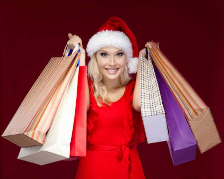 Pretty girl in Christmas cap hands shopping packets, isolated on purple photo