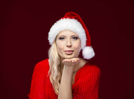 x mas: Pretty woman in Christmas cap blows kiss, isolated on purple Stock Photo