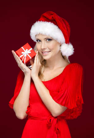 Beautiful woman in Christmas cap hands a present, isolated on purple Stock Photo - 16440848