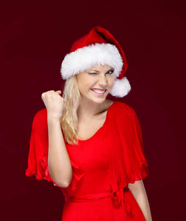 Beautiful woman in Christmas cap is very happy, isolated on purple photo