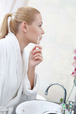 Attractive woman washes face with lotion using wadding stick photo
