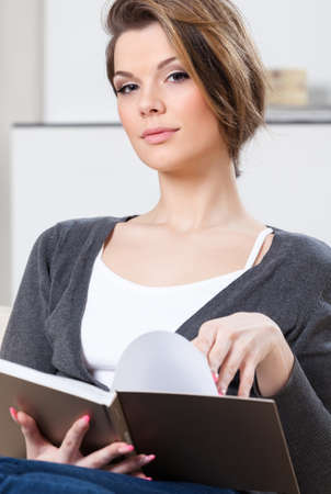Attractive woman reads the book sitting on the white leather sofa photo