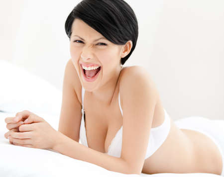 Woman in underwear is lying in the wonderful bed, white background photo