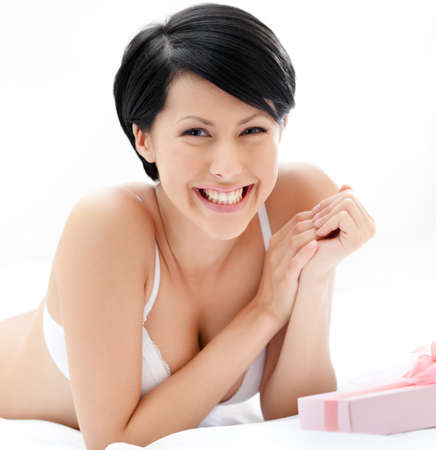 womans: Woman in underwear finds a present in bed, white background Stock Photo
