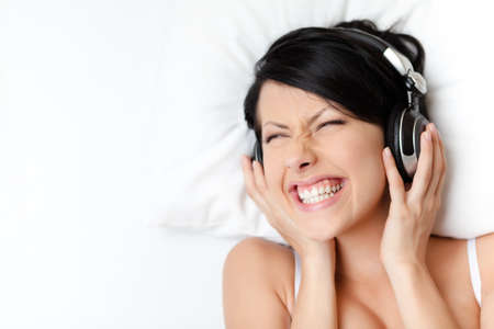 Woman in underwear listens to music through the earphones, white background Stock Photo - 16440871