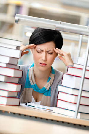 Tired girl with headache sitting at the desk surrounded with piles of books Stock Photo - 16440842