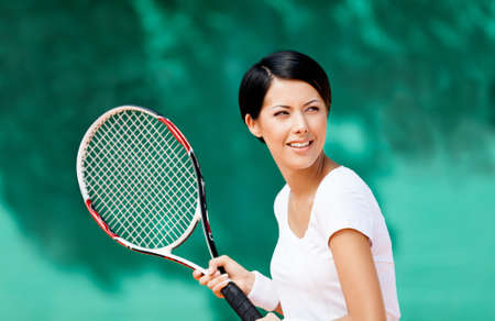 Portrait of tennis player with racket at the tennis court photo