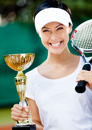 Female tennis player won the cup at the sport competition. Prize photo