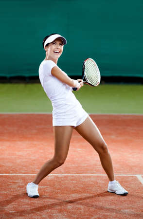 Tennis training. Female player at the clay tennis court photo