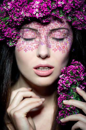 Close up portrait of model with flowered wreath and fashion make up with eyes closed photo