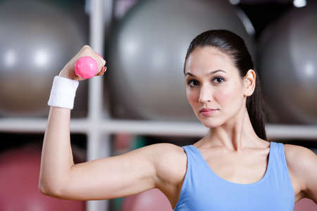 Sportswoman training with dumbbells in gym. Physical strength and developing muscles Stock Photo - 16440720