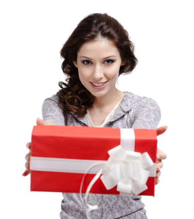 Young woman reaches out a gift wrapped in red paper, isolated on white photo